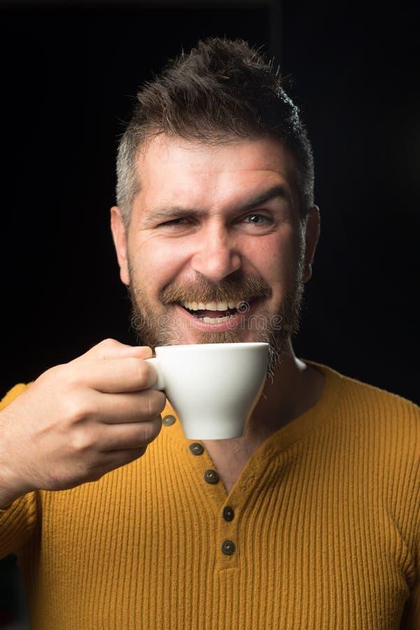 Być w kawowym nastroju Szczęśliwy modniś pije kawę w ranku Brodaty mężczyzna ono uśmiecha się z filiżanką dla śniadania fotografia royalty free