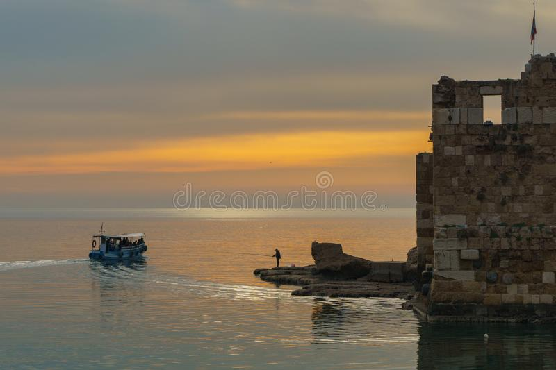 BYBLOS - LEBANON - A man fishing near a tourist boat at sunset in Byblos harbour Lebanon 5 february 2018 stock image
