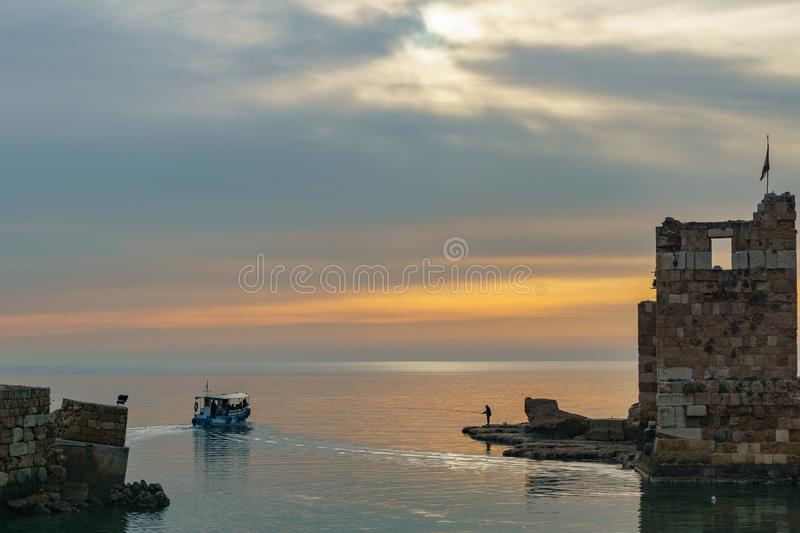 BYBLOS - LEBANON - A man fishing near a tourist boat at sunset in Byblos harbour Lebanon 5 february 2018 royalty free stock photos
