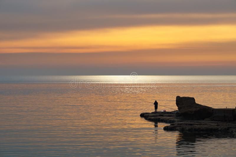 BYBLOS - LEBANON - A man fishing near a tourist boat at sunset in Byblos harbour Lebanon 5 february 2018 stock photography
