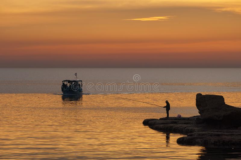 BYBLOS - LEBANON - A man fishing near a tourist boat at sunset in Byblos harbour Lebanon 5 february 2018 royalty free stock images
