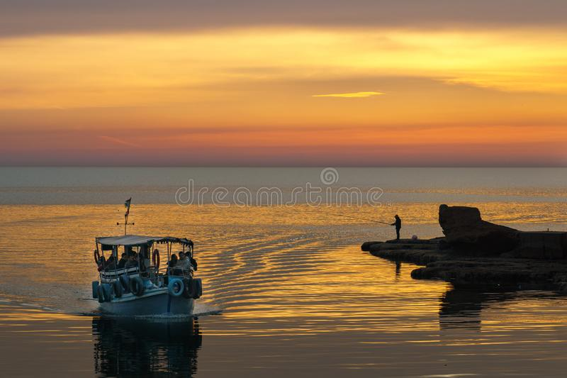 BYBLOS - LEBANON - A man fishing near a tourist boat at sunset in Byblos harbour Lebanon 5 february 2018 stock photos