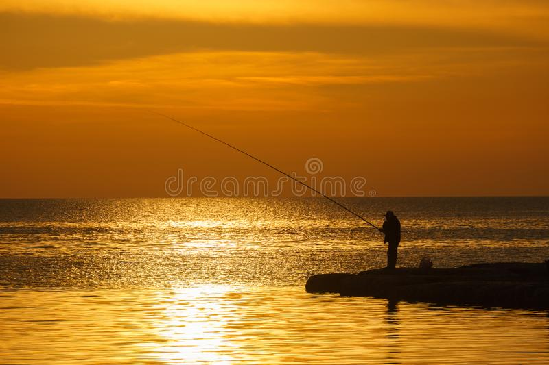BYBLOS - LEBANON - A man fishing at sunset in Byblos harbour Lebanon 5 february 2018 stock images