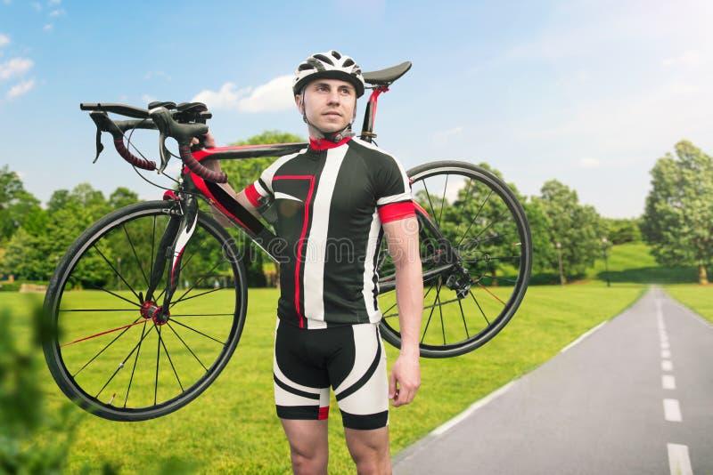 Bycyclist在骑自行车以后保留在肩膀的自行车 免版税库存图片