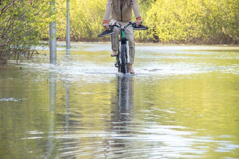 Bycyclist med naken fot försöker att övervinna vatten under en flod i vår arkivbild