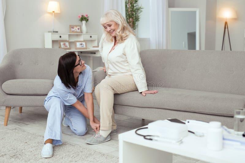 Bycza pielęgniarka dostaje kapcie dla starej kobiety zdjęcia stock