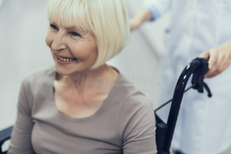 Bycza starzejąca się kobieta jest poruszająca na pushchair z asystentem obraz royalty free