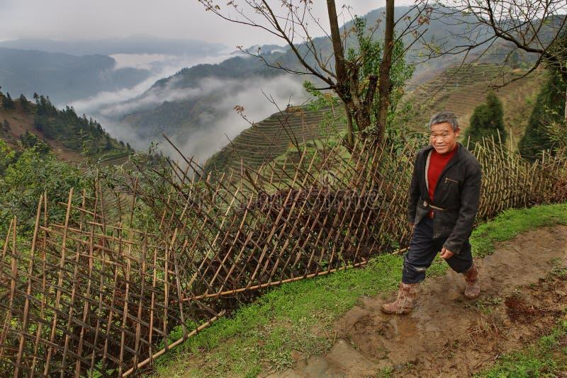 Bygd bergiga Kina, bonde, promenerar ett vide- staket. arkivbilder