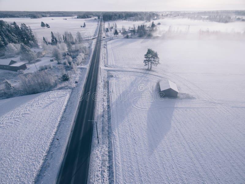 Bygd på snöig vinterdag Flyg- sikt av byn och vägen på vintern arkivbild