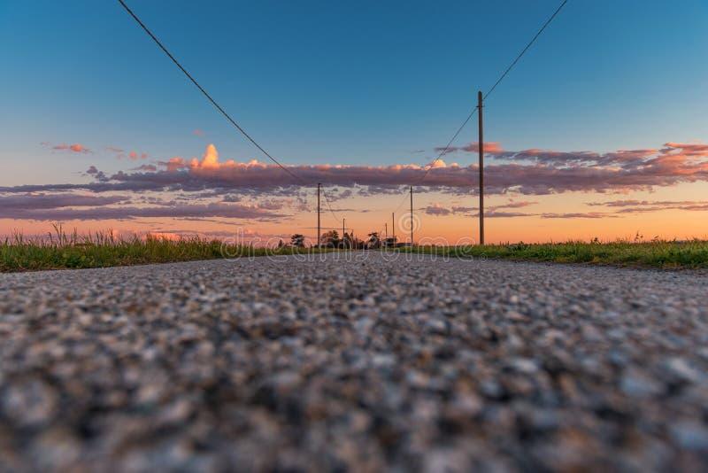 Bygdväg i solnedgångtid royaltyfri fotografi