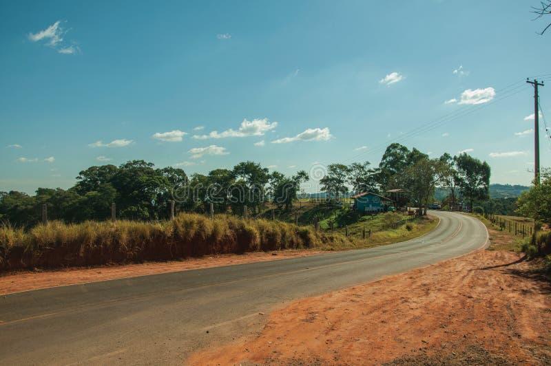 Bygdväg på landskapet som täckas av ängar och träd fotografering för bildbyråer