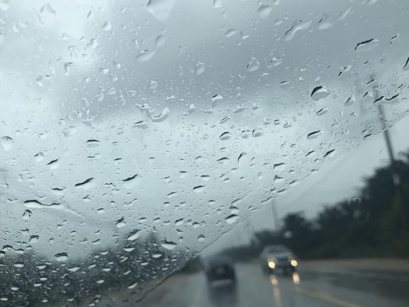 Bygdvägsikt från vindrutan för framdel för bil` s som fokuserar på regndroppar arkivfoto