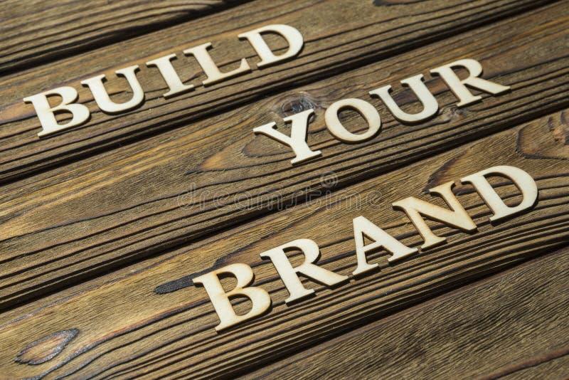 Bygg din märkestext komponeras av bokstäver på en träbakgrund royaltyfri bild