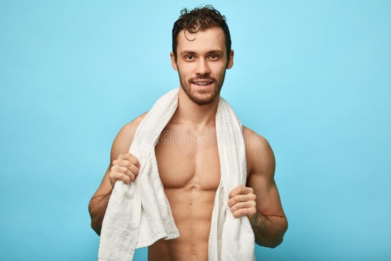 Bygg väl den enorma lyckliga stiliga mannen med en handduk runt om hals arkivfoto