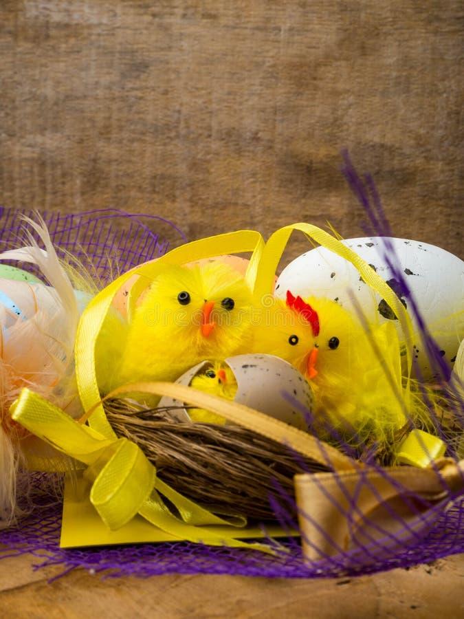 Bygga bo dekorativ sammansättning för påsken med gula hönor, färgägg och färgrika fjädrar på träbräde arkivbilder