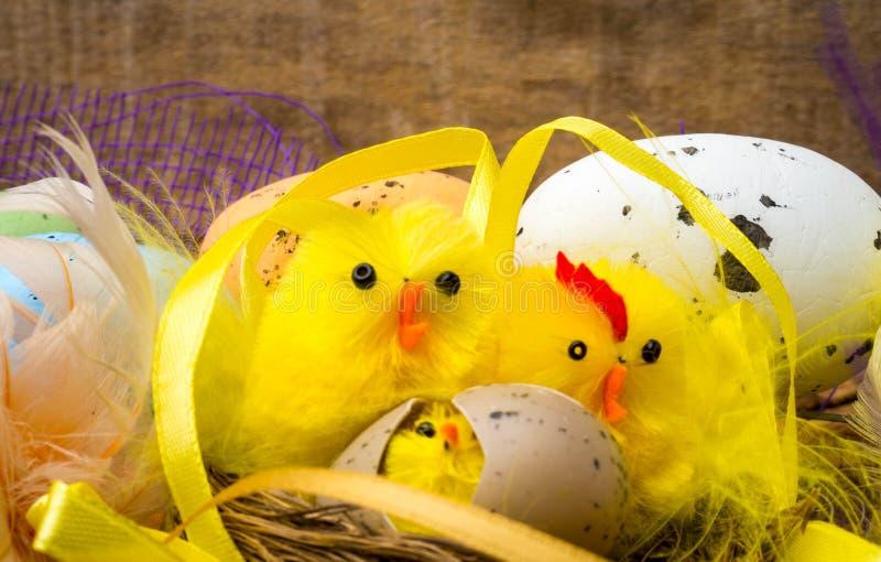 Bygga bo dekorativ sammansättning för påsken med gula hönor, färgägg och färgrika fjädrar på träbräde royaltyfri bild