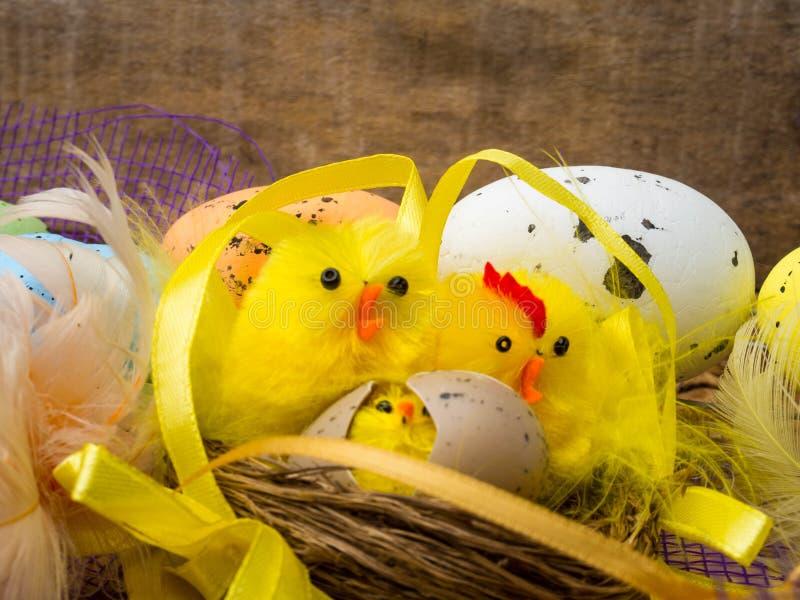 Bygga bo dekorativ sammansättning för påsken med gula hönor, färgägg och färgrika fjädrar på träbräde royaltyfri foto