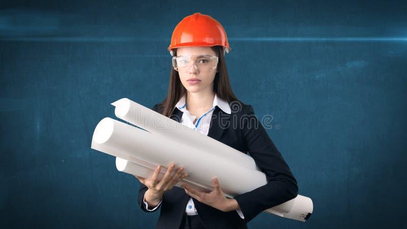 Bygga, framkallnings-, consrtuction- och arkitekturbegrepp - affärskvinna i orange hjälm med exponeringsglas och ritningen arkivbilder