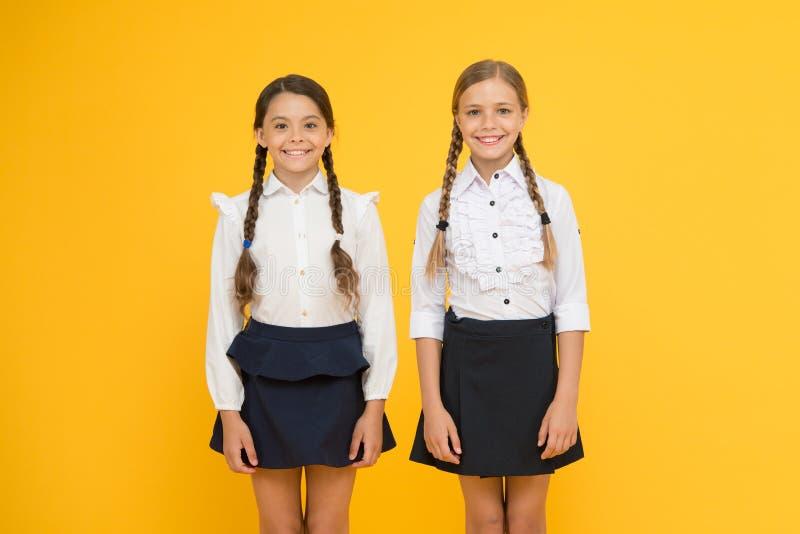 Byggande av en ljusare framtid för barn Lyckligt le för gulliga små skolflickor på gul bakgrund G? tillsammans fotografering för bildbyråer