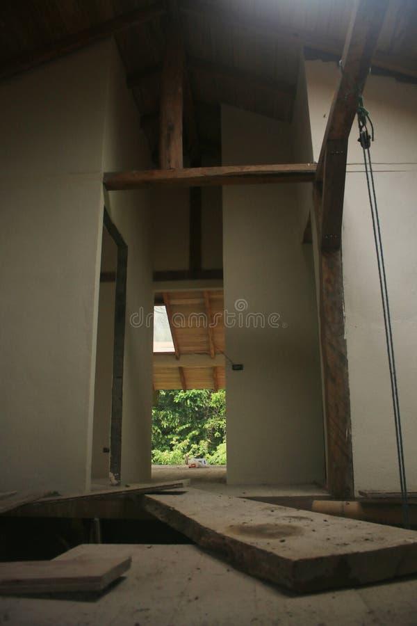 Byggande av ett hus med en träbro för planka så mellan två oavslutade delar royaltyfri foto