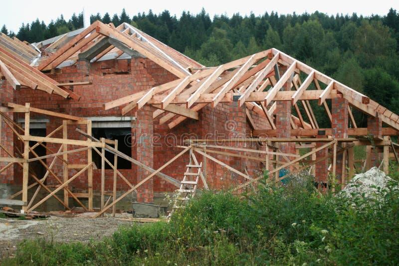 Byggande av ett hus av röd tegelsten Montering av taket från träbräden arkivbild