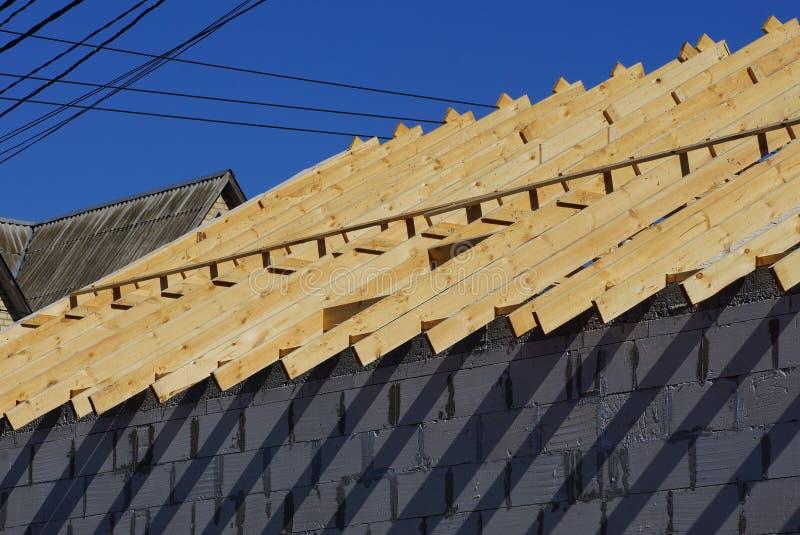 Byggande av ett hus av träplankor och gråa tegelstenar mot en blå himmel royaltyfri bild