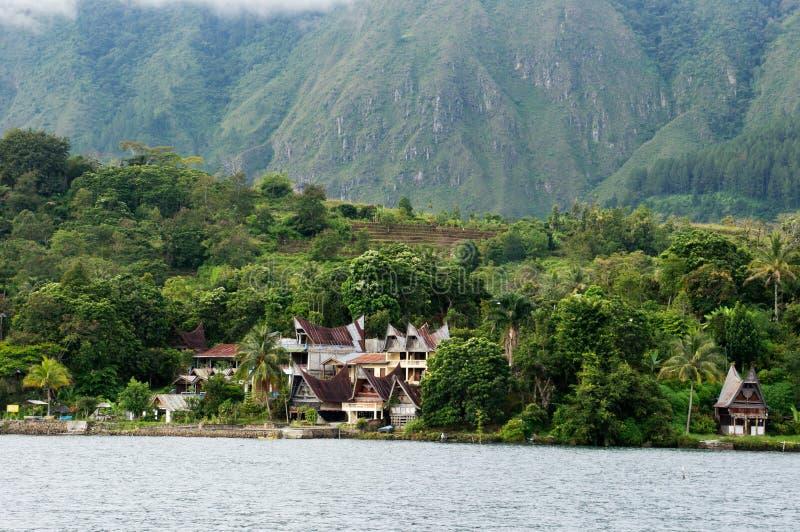 Byggande för flera hus på foten av ett berg bredvid en sjö i den Sumatra Samosir ön fotografering för bildbyråer
