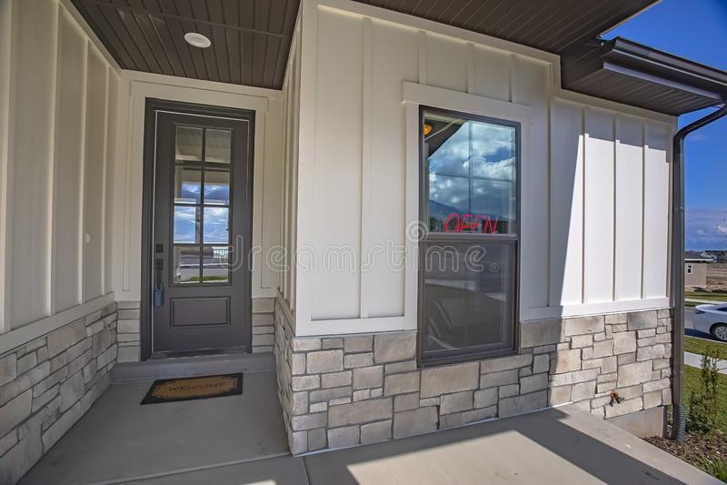 Byggande fasad med den exponeringsglas försåg med rutor dörren och en kombination av tegelsten- och träväggen royaltyfria foton