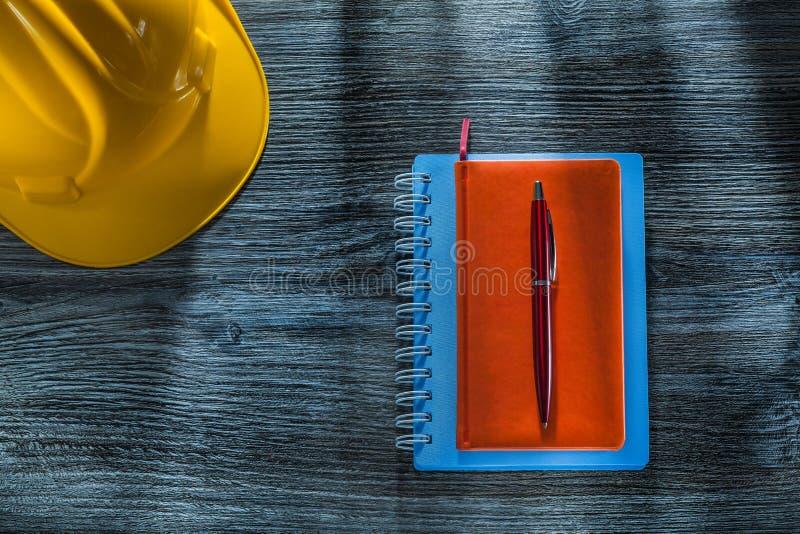Byggande hjälm för ny notepadspenna på träbräde royaltyfri fotografi