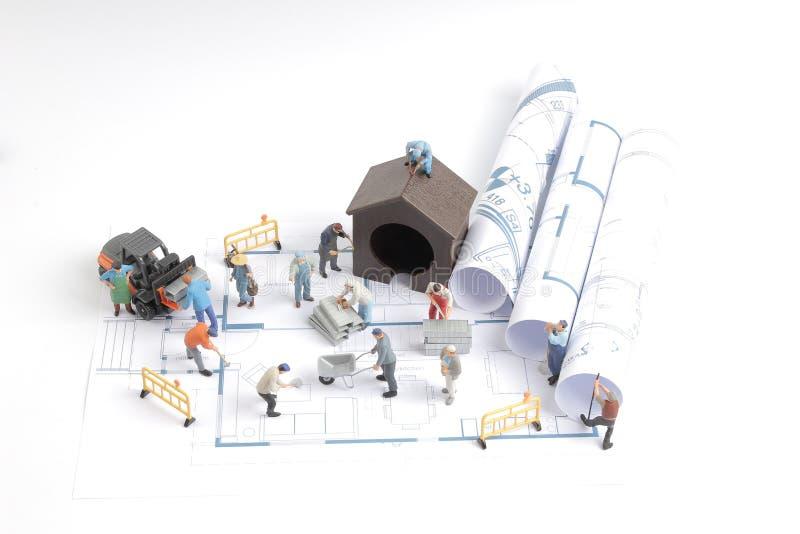 byggande hus på ritningar med arbetarkonstruktion fotografering för bildbyråer