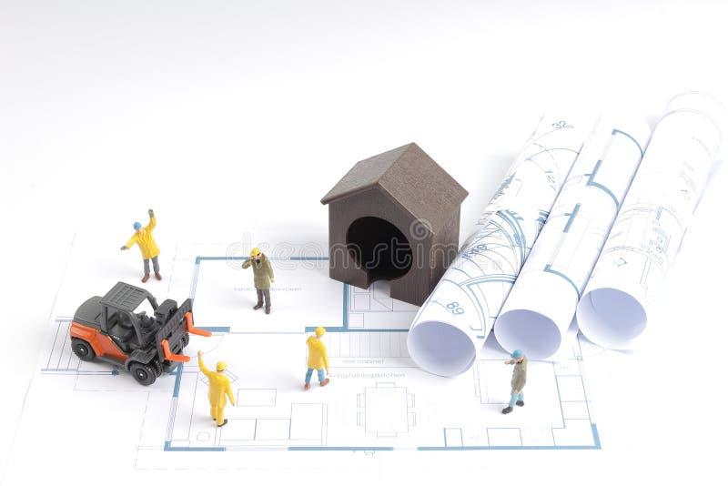 byggande hus på ritningar med arbetarkonstruktion arkivfoton