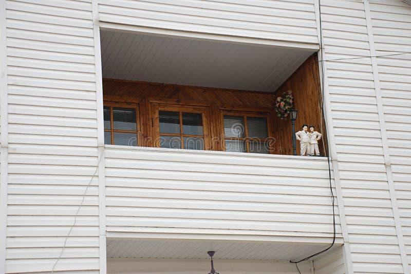 Byggande lofthuskonstruktion med asbesttaket, den hemtrevliga balkongen och sidfasaden arkivfoto