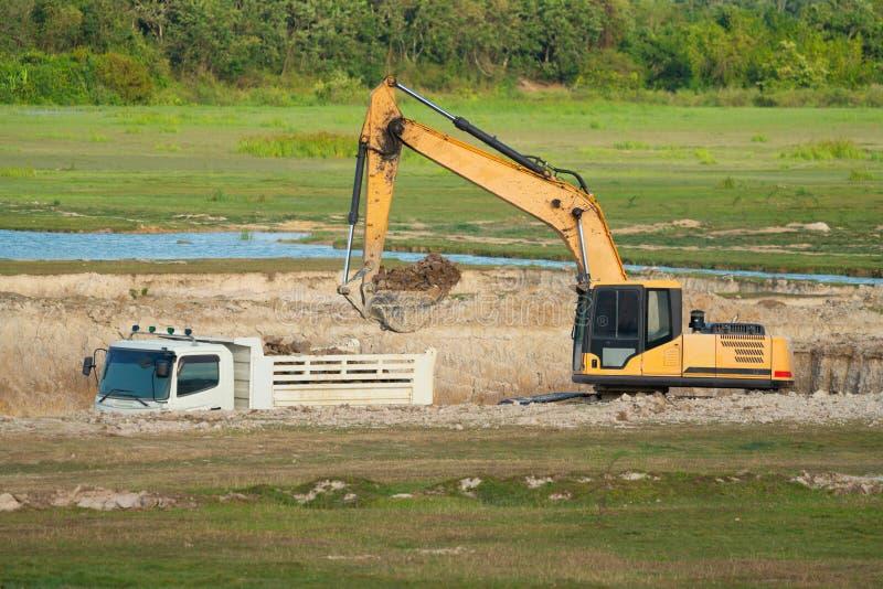 Byggande maskiner: Grävarepäfyllning åker lastbil med jord royaltyfri bild