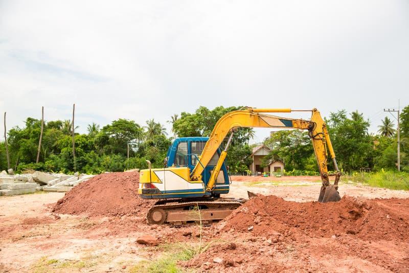 Byggande maskiner: Grävarepäfyllning åker lastbil med jord Grävskopapäfyllningssand in i en dumper fotografering för bildbyråer