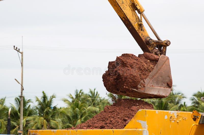 Byggande maskiner: Grävarepäfyllning åker lastbil med jord Grävskopapäfyllningssand in i en dumper royaltyfria bilder