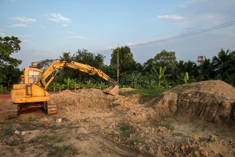 Byggande maskiner: Grävarepäfyllning åker lastbil med jord Grävskopapäfyllningssand in i en dumper Arbete i villebrådet arkivfoton