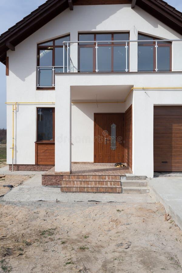 Byggande nytt hus med keramiskt det tegelplattataklägga, garaget och balkongen arkivbilder