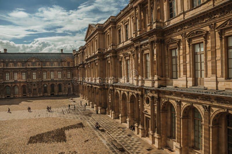 Byggande och inre borggård med folk på Louvremuseet i Paris arkivbild