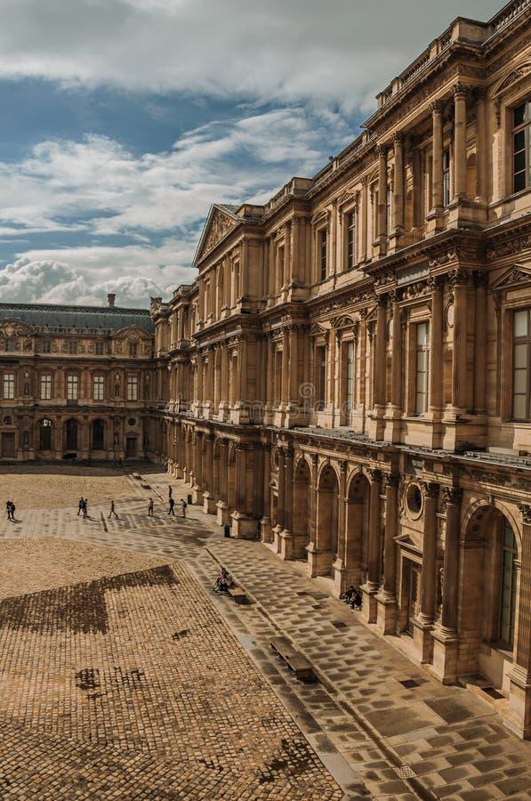 Byggande och inre borggård med folk på Louvremuseet i Paris royaltyfri foto