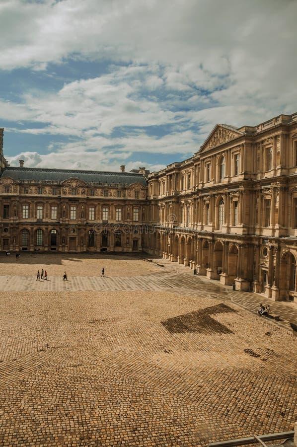 Byggande och inre borggård med folk på Louvremuseet i Paris royaltyfria foton