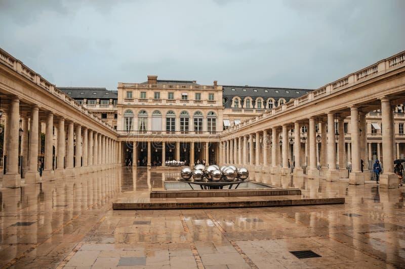 Byggande och inre borggård med modern skulptur på regnig dag på Palais-Royal i Paris arkivbild