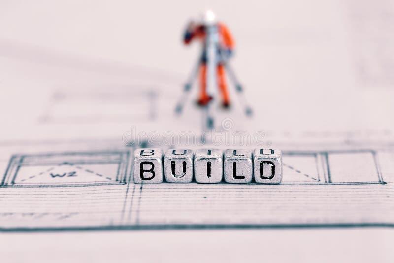 Byggande plan med ordbyggandet på pärlor och en modellarbetare arkivfoton