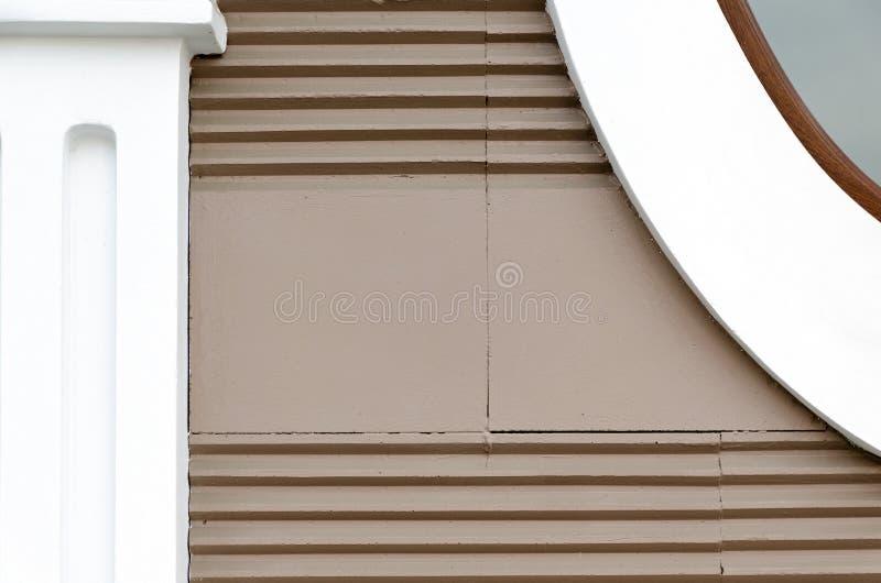 Byggande väggbruntfärg med horisontalband, beståndsdelar av fasaden - pilaster av enkla former royaltyfri foto