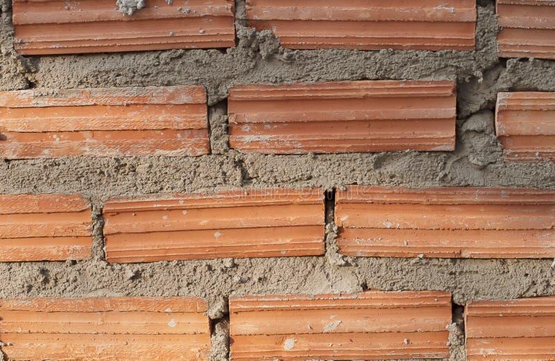 Byggandevägg och staket från lerategelsten arkivfoton