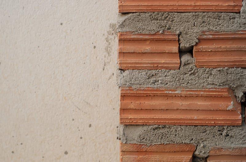 Byggandevägg och staket från lerategelsten royaltyfria foton