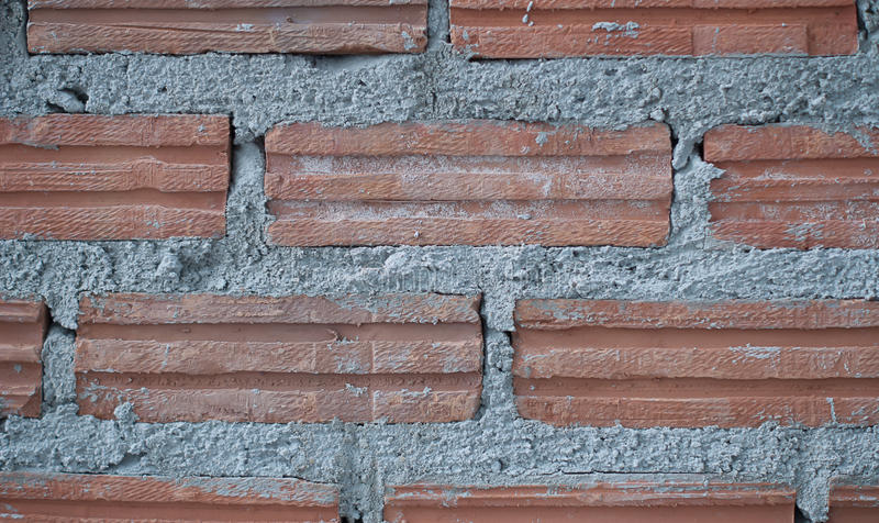 Byggandevägg och staket från lerategelsten arkivbild