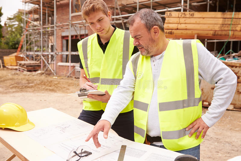 Byggmästare On Building Site som diskuterar arbete med lärlingen royaltyfri bild