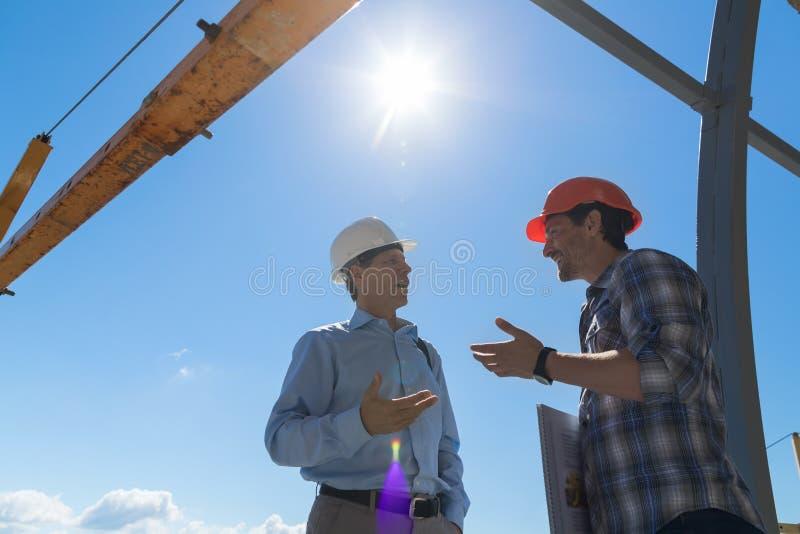 Byggmästare And Business Man som utomhus diskuterar projektmöte på Buiding konstruktionsplats arkivfoton