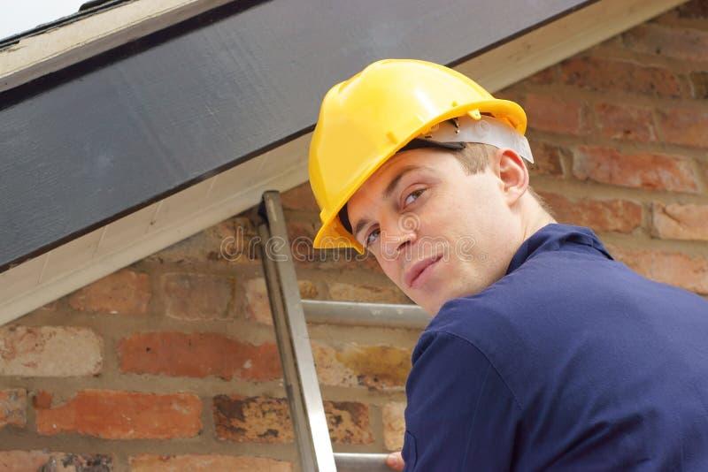 Byggmästare eller roofer på en stege royaltyfria bilder
