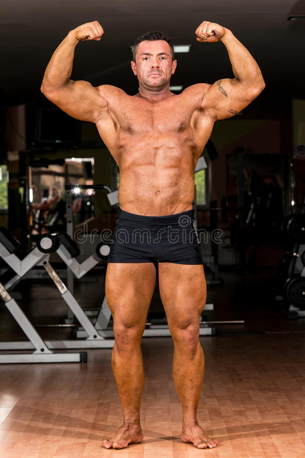 Byggmästare för muskulös kropp som visar hans främre dubbla biceps royaltyfria bilder